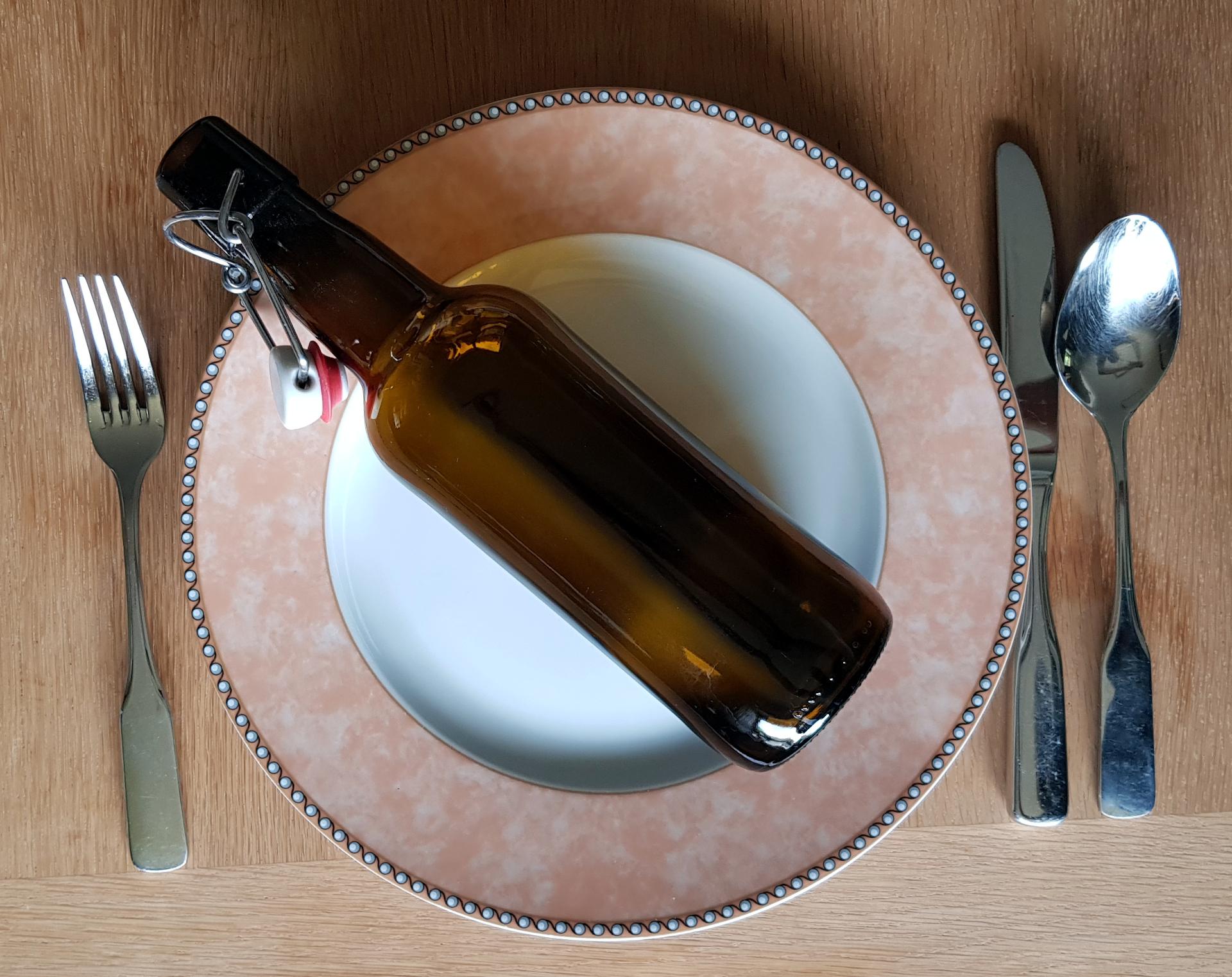 Kalorien, kcal und kJ - Nährwertangaben. Bierflasche auf leerem Teller mit Besteck
