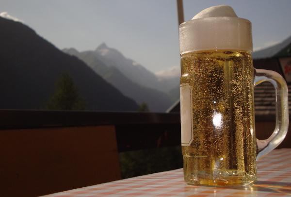 Helles Bier im Krug in der Abendsonne und im Hintergrund das Glocknermassiv.