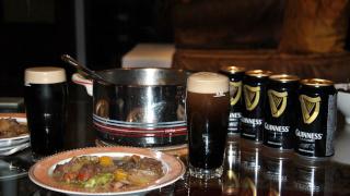 Ein Foto von einem Irish Stew und einem Glas Guinness mit Guinness Dosen im Hintergrund.